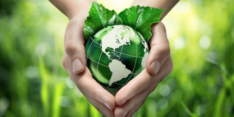 Hands holding green globe graphic