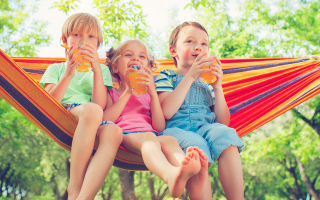 Kids sipping juice in hammock