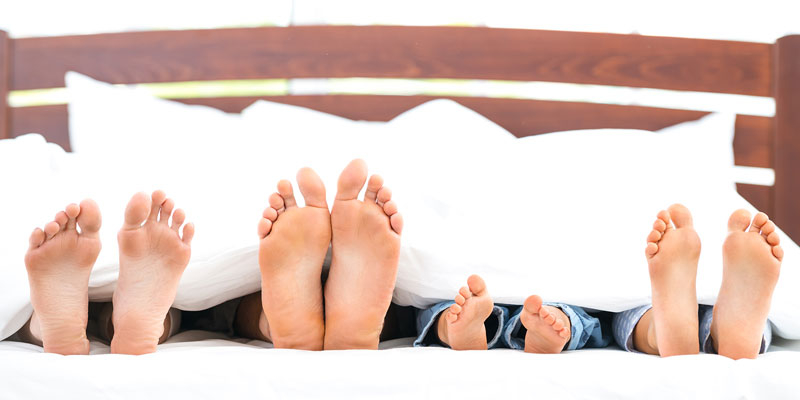 Family's feet sticking out from bottom of bed
