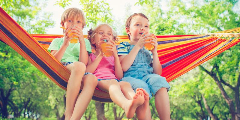 Kids sipping juice in hammock